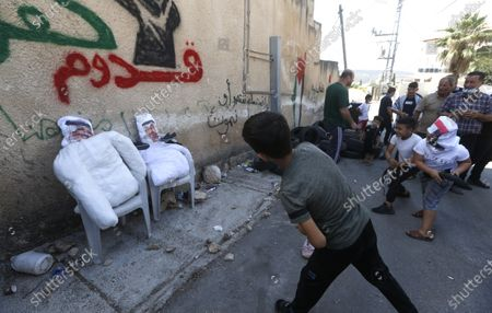 Palestinian protesters throw shoes at effigies depicting Abu Dhabi Crown Prince Mohammed bin Zayed al-Nahyan and King of Bahrain Hamad bin Isa bin Salman Al Khalifa during a demonstration against Israel's settlements in the village of Kofr Qadom near the northern West Bank city of Nablus, 25 September 2020.