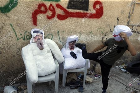 Palestinian protester hits effigies depicting Abu Dhabi Crown Prince Mohammed bin Zayed al-Nahyan and King of Bahrain Hamad bin Isa bin Salman Al Khalifa during a demonstration against Israel's settlements in the village of Kofr Qadom near the northern West Bank city of Nablus, 25 September 2020.