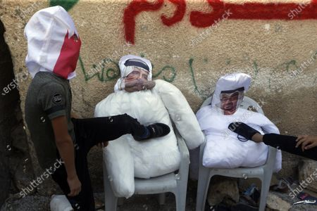 Palestinian protesters hit effigies depicting Abu Dhabi Crown Prince Mohammed bin Zayed al-Nahyan and King of Bahrain Hamad bin Isa bin Salman Al Khalifa during a demonstration against Israel's settlements in the village of Kofr Qadom near the northern West Bank city of Nablus, 25 September 2020.