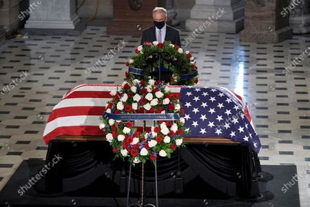 Stock Image of Sen. Tim Kaine, D-Va., pays respects at the flag-draped casket of Justice Ruth Bader Ginsburg lying in state in Statuary Hall of the U.S. Capitol, in Washington. Ginsburg died at the age of 87 on Sept. 18 and is the first women to lie in state at the Capitol