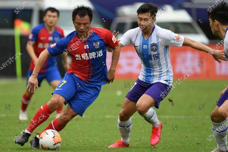 Gao Xiang (L) of Qingdao Huanghai vies the ball during the 13th round match between Qingdao Huanghai and Tianjin Taida at the postponed 2020 season Chinese Football Association Super League (CSL) Suzhou Division in Suzhou, east China's Jiangsu Province, Sept. 25, 2020.