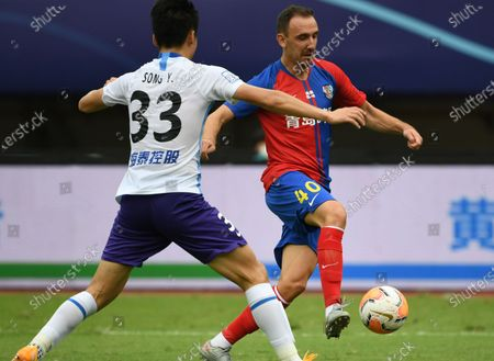 Popovic (R) of Qingdao Huanghai vies the ball during the 13th round match between Qingdao Huanghai and Tianjin Taida at the postponed 2020 season Chinese Football Association Super League (CSL) Suzhou Division in Suzhou, east China's Jiangsu Province, Sept. 25, 2020.
