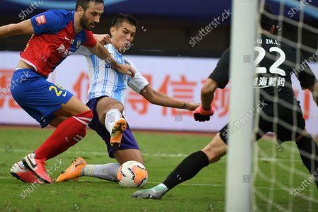 Xiao Zhi (C) of Tianjin Taida shoots past Vukovic (L) of Qingdao Huanghai during the 13th round match between Qingdao Huanghai and Tianjin Taida at the postponed 2020 season Chinese Football Association Super League (CSL) Suzhou Division in Suzhou, east China's Jiangsu Province, Sept. 25, 2020.