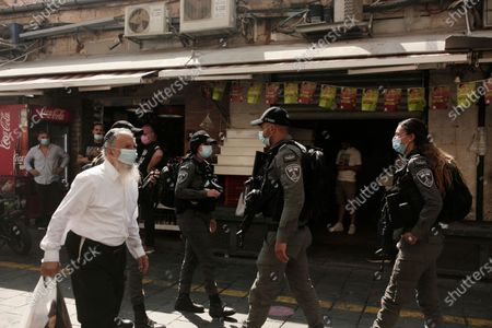 Stock Photo of Israeli Border Police officers patrol the Machane Yehuda market as vendors begin to close their stalls in Jerusalem, during the start of new restrictions in the three-week nationwide lockdown in Israel, the country's second, to curb the spread of the coronavirus