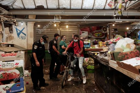 Bicyclist passes Israeli police officers talking to a vendor in the Machane Yehuda market in Jerusalem, during the start of new restrictions in the three-week nationwide lockdown in Israel, the country's second, to curb the spread of the coronavirus