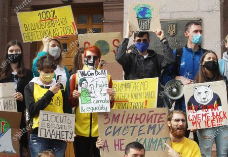Stockfoto van Protesters hold placards expressing their opinion during the demonstration outside City Hall in Kiev. Climate activists all over the globe united for the first global climate strike action of 2020 held worldwide amid the COVID-19 coronavirus pandemic. The Global Day of Climate Action is a part of student protest, the Fridays for Future movement aiming to spark the world leaders into action on climate change.