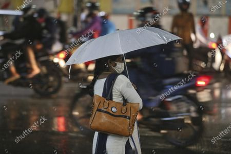 Stockafbeelding van An Indian woman wearing a face mask to prevent the spread of the coronavirus waits to cross a street as it rain in Hyderabad, India, . India receives its monsoon rains from June to September