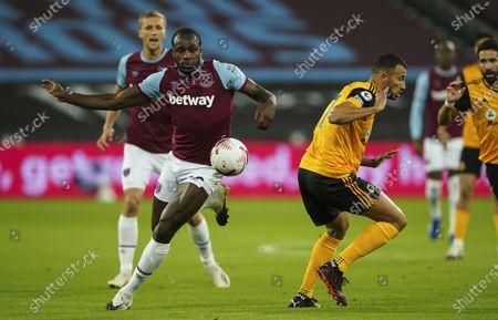 Michail Antonio of West Ham United turns Romain Saiss of Wolverhampton Wanderers