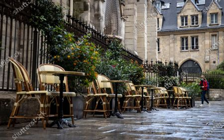 A pedestrian wearing protective a face mask walks past a deserted bistrot terrace at lunch time, in the latin quarter in central Paris, France, 25 September 2020. Cases  of coronavirus SARS-CoV-2 which causes the Covid-19 disease have surged to over 16,000 new cases recorded in a 24 hour period in France. The French government has announced new measures to be implemented in zones of active circulation for the virus, dubbed Ôred zonesÕ. The measures include limiting gatherings to 10 people or less, and imposing a 10pm curfew on bars and restaurants - an initiative which is facing push-back from restaurant and bar owners who claim their livelihoods are already at stake following the total lockdown earlier in the year.