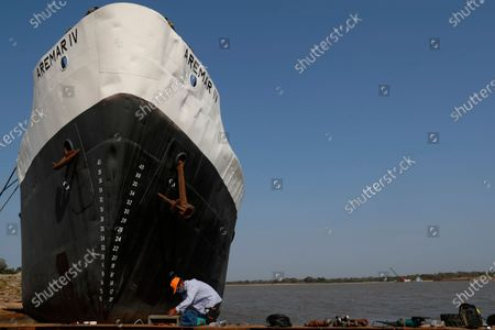 Technician Oscar Riquelme works on the maintenance of a ship taking advantage of the extremely low water levels of the Paraguay River, that makes navigation for the ships impossible, in Asuncion, Paraguay