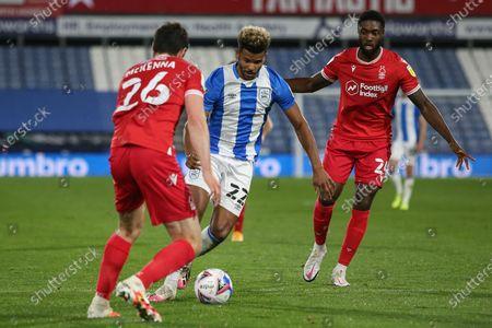 Fraizer Campbell (22) of Huddersfield Town runs at Scott McKenna (26) of Nottingham Forest