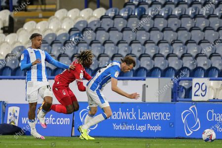 Stock Image of Alex Mighten (17) of Nottingham Forest and Richard Stearman (12) of Huddersfield Town stumble while challenging for the ball