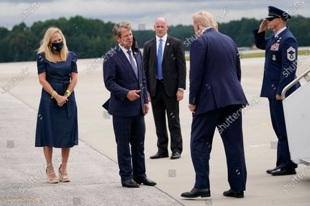 President Donald Trump greets Georgia Gov. Brian Kemp and his wife Marty, left, as he arrives at Dobbins Air Reserve Base for a campaign event at the Cobb Galleria Centre, in Atlanta