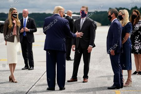 Stock Photo of President Donald Trump talks with Georgia Gov. Brian Kemp and his wife Marty, right, Sen. David Perdue, R-Ga., center, and Sen. Kelly Loeffler, R-Ga., as he arrives at Dobbins Air Reserve Base for a campaign event at the Cobb Galleria Centre, in Atlanta