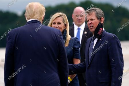 Stock Image of President Donald Trump greets Georgia Gov. Brian Kemp and his wife Marty as he arrives at Dobbins Air Reserve Base for a campaign event at the Cobb Galleria Centre, in Atlanta