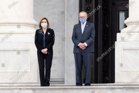 House Speaker Nancy Pelosi (D-CA) and Senate Minority Leader Chuck Schumer (D-NY) wearing face masks wait for the casket of Ruth Bader Ginsburg's Casket to be brought Into the U.S. Capitol.