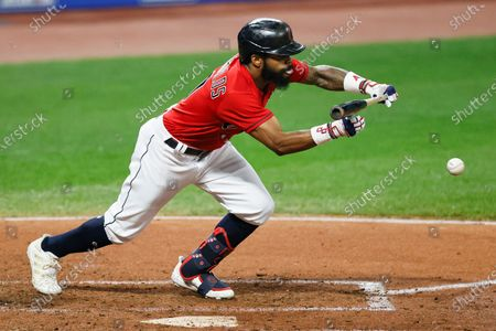 Cleveland Indians' Delino DeShields bunts for a base hit off Pittsburgh Pirates relief pitcher Sam Howard during the seventh inning of a baseball game, in Cleveland