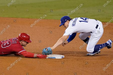 Los Angeles Angels' Max Stassi, left, is safe at second base as Los Angeles Dodgers second baseman Enrique Hernandez makes a late tag after Stassi doubled during the fourth inning of a baseball game, in Los Angeles