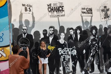 A woman is seen taking a picture of another woman in front of the mural. A powerful mural of people, who have impacted peoples lives in and out of the U.S. is seen on a street in Wynwood, the art district of Miami. CDC Shutters Dining and Bars, saying it's risky due to the spread of COVID-19.