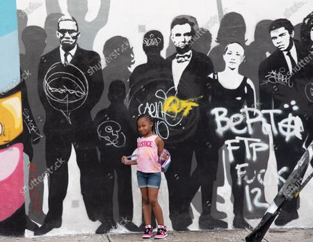 Sydney Chenault is seen in front of the mural. Sydney and her family traveled in to Miami on vacation. A powerful mural of people, who have impacted peoples lives in and out of the U.S. is seen on a street in Wynwood, the art district of Miami. CDC Shutters Dining and Bars, saying it's risky due to the spread of COVID-19.