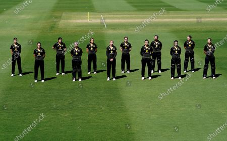 Australian players stand during a minutes silence as a mark of respect to the passing of former Australian cricketer Dean Jones prior to the T20 International match between Australia and New Zealand at Allan Border Field in Brisbane, Australia, 26 September 2020.