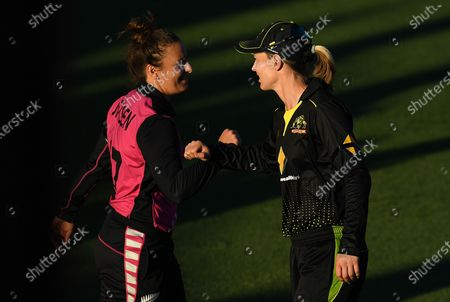 Australian captain Meg Lanning (R) reacts with New Zealand player Hayley Jensen following the T20 International match between Australia Women and New Zealand Women at Allan Border Field in Brisbane, Australia, 26 September 2020.