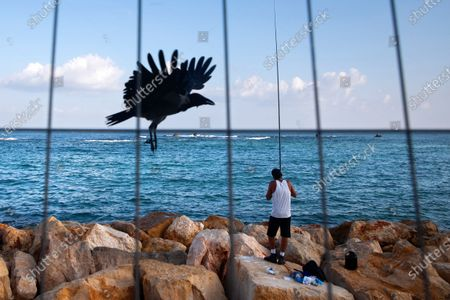 Fisherman casts his rod at the Mediterranean Sea shore during a three-week nationwide lockdown, in Tel Aviv, Israel