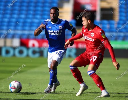 Junior Hoilett of Cardiff City moves forward with the ball as Araruna of Reading comes in for the challenge; Cardiff City Stadium, Cardiff, Glamorgan, Wales; English Football League Championship Football, Cardiff City versus Reading.