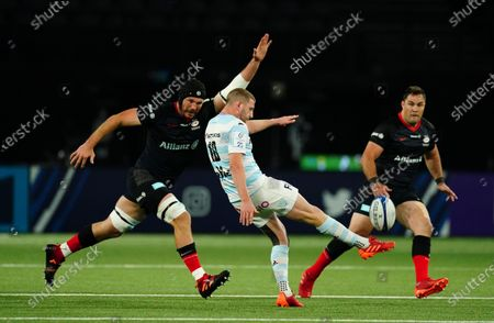 Finn Russell of Racing 92 clears under pressure from Tim Swinson of Saracens