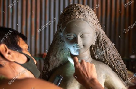 Stock Photo of A Bangladeshi artist works on an idol of the Goddess Durga ahead of the largest Durga Puja festival of the Bengali Hindus community in Dhaka, Bangladesh, 26 September 2020. The Durga puja will run from 22 to 26 October. According to Hindu faith, goddess Durga comes down to the earth from the heaven to establish peace, harmony by annihilating evil forces.