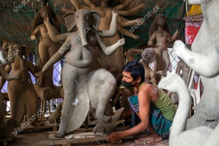 Stock Picture of A Bangladeshi artist works on an idol of the God Ganesha ahead of the largest Durga Puja festival of the Bengali Hindus community in Dhaka, Bangladesh, 26 September 2020. The Durga puja will run from 22 to 26 October. According to Hindu faith, goddess Durga comes down to the earth from the heaven to establish peace, harmony by annihilating evil forces.