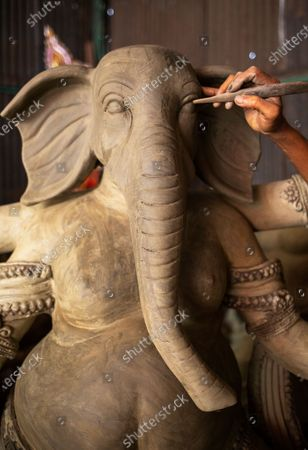 Stock Image of A Bangladeshi artist works on an idol of the God Ganesha ahead of the largest Durga Puja festival of the Bengali Hindus community in Dhaka, Bangladesh, 26 September 2020. The Durga puja will run from 22 to 26 October. According to Hindu faith, goddess Durga comes down to the earth from the heaven to establish peace, harmony by annihilating evil forces.