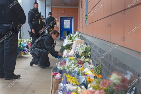 An armed police officer laying flowers for Sgt Matt Ratana at Croydon Custody Centre. A murder investigation has been launched by police after the death of custody police sergeant Matt Ratana at the Croydon Custody Centre in South London yesterday.Photo credit:Grant Falvey/LNP