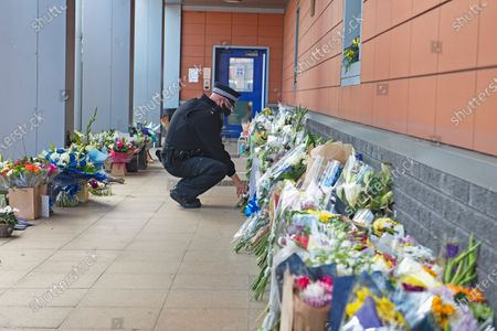 A police officer laying flowers for Sgt Matt Ratana at Croydon Custody Centre. A murder investigation has been launched by police after the death of custody police sergeant Matt Ratana at the Croydon Custody Centre in South London yesterday.Photo credit:Grant Falvey/LNP