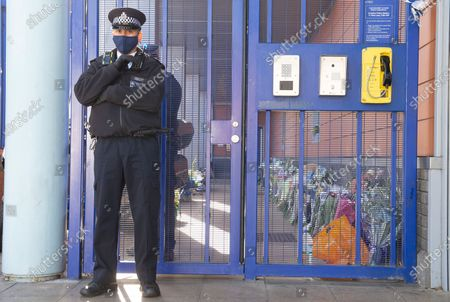 Police stand guard at a flower memorial for Sgt Matt Ratana at Croydon Custody Centre this morning. A murder investigation has been launched by police after the death of custody police sergeant Matt Ratana at the Croydon Custody Centre in South London yesterday.Photo credit:Grant Falvey/LNP