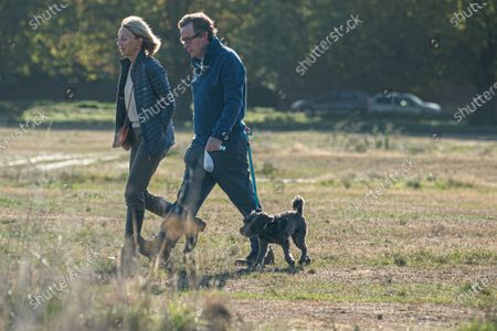 People walking their dog  in the morning sunshine on Wimbledon Common
