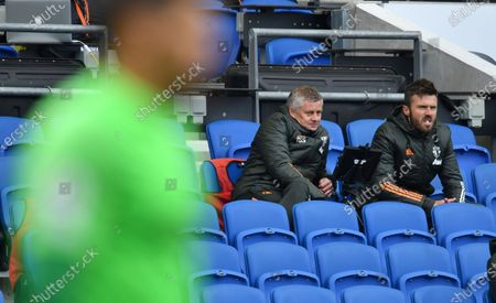Manchester United's manager Ole Gunnar Solskjaer, left sits with his assistant Michael Carrick as they watch their players during the English Premier League soccer match between Brighton Hove Albion and Manchester United in Brighton, England