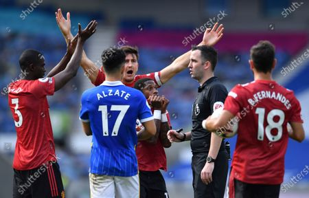 Manchester United's Fred, center with teammates Manchester United's Harry Maguire, at rear and Manchester United's Eric Bailly, left, appeal to the referee Chris Kavanagh for a penalty for hand ball against Brighton's Neal Maupay during the English Premier League soccer match between Brighton Hove Albion and Manchester United in Brighton, England, . The penalty was given after a VRA review and United won the game 3-2 with the last kick if the match