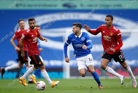 Stock Photo of Brighton's Adam Lallana, center, holds off a challenge by Manchester United's Mason Greenwood, right, during the English Premier League soccer match between Brighton Hove Albion and Manchester United in Brighton, England