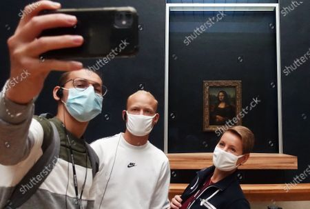 """People wearing face masks take a selfie with the famous painting """"Mona Lisa"""" at the Louvre Museum in Paris, France, Sept. 25, 2020. The number of confirmed cases of COVID-19 in France rose to 513,034 with 15,797 new cases in the past 24 hours, according to the latest data released by the Health Ministry on Friday."""