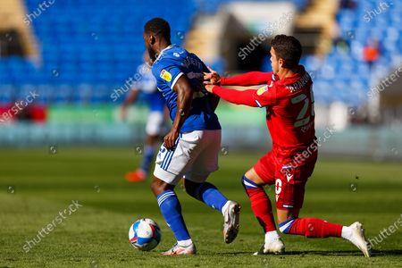 Cardiff City midfielder Junior Hoilett (33) is pushed by Reading midfielder Felipe Araruna Hoffmann (20) during the EFL Sky Bet Championship match between Cardiff City and Reading at the Cardiff City Stadium, Cardiff