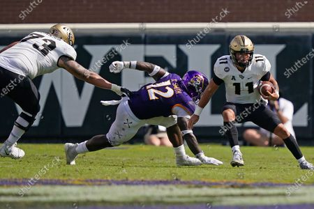 Central Florida quarterback Dillon Gabriel (11) scrambles against East Carolina linebacker Xavier Smith (12) as Central Florida offensive lineman Samuel Jackson (73) defends during the second half of an NCAA college football game in Greenville, N.C
