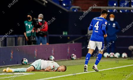 Schalke's Ozan Kabak, right, has fouled Bremen's Ludwig Augustinsson, left, during the German Bundesliga soccer match between FC Schalke 04 and Werder Bremen in Gelsenkirchen, Germany, . Kabak is suspected to spit on Augustinsson in that scene