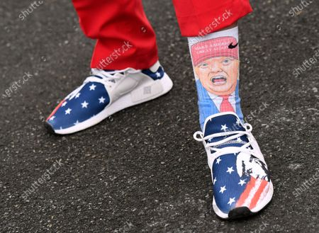 Andrew Wright, 19, of Newport, Pa., a supporter of President Donald Trump, shows off his shoes and socks before a Trump campaign rally at Harrisburg International Airport, in Middletown, Pa