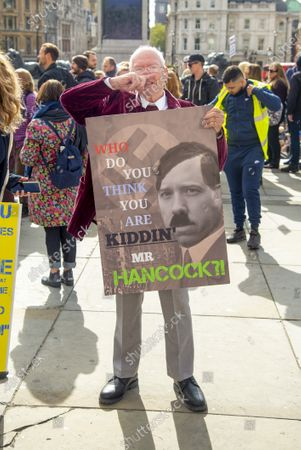 A man holding a placard with Matt Hancocks depicted as Adolf Hitler during the 'We Do Not Consent' protests in Trafalgar Square London against Lockdown, Social Distancing, Track and Trace & wearing of face masks.