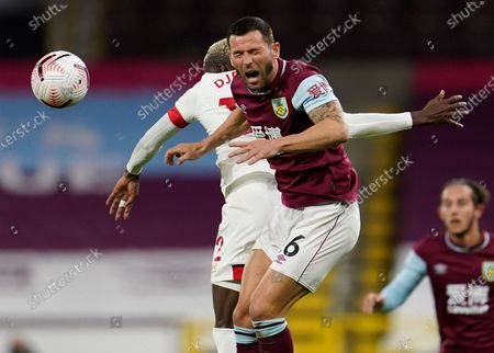 Burnley's Phil Bardsley, right, reacts as he battles for the ball with Southampton's Moussa Djenepo during the English Premier League soccer match between Burnley and Southampton at Turf Moor in Burnley, England