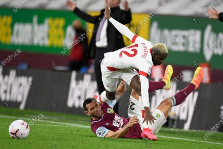 Southampton's Moussa Djenepo, top, is tackled by Burnley's Phil Bardsley during the English Premier League soccer match between Burnley and Southampton at Turf Moor in Burnley, England