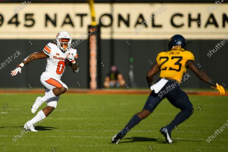 Oklahoma State running back LD Brown (0) watches West Virginia's Tykee Smith (23) during an NCAA college football game, in Stillwater, Okla