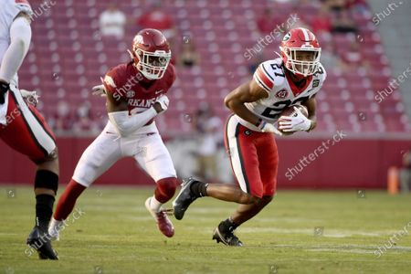 Georgia defensive back Eric Stokes (27) intercepts a pass intended for Arkansas' Mike Woods, left, during the second half of an NCAA college football game in Fayetteville, Ark