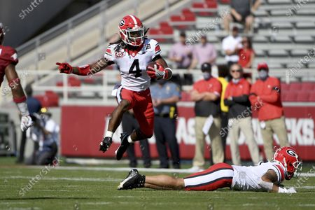 Georgia running back James Cook (4) jumps over a teammate during the first half of an NCAA college football game against Arkansas in Fayetteville, Ark